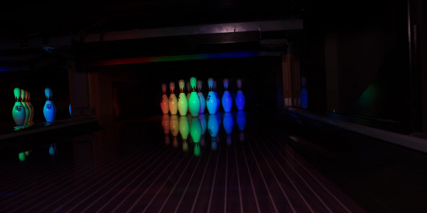 Bowling pins glowing under lasers and black lights